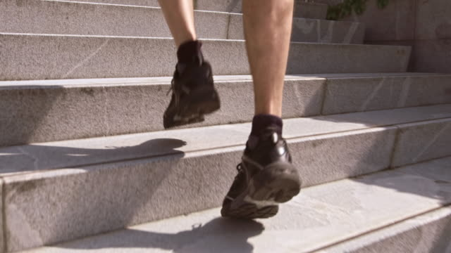 SLO MO TS Man jogging up stairs and alongside building