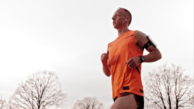 slo mo ts man jogging with earphones on - one mid adult man only stock videos & royalty-free footage