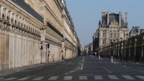 man jogs on a nearly empty street in paris, france during the coronavirus pandemic. - healthcare and medicine or illness or food and drink or fitness or exercise or wellbeing stock videos & royalty-free footage