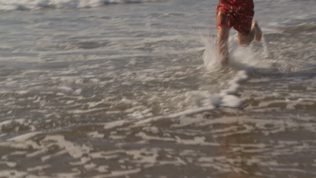 man jogs through the water at the beach - badeshorts stock-videos und b-roll-filmmaterial