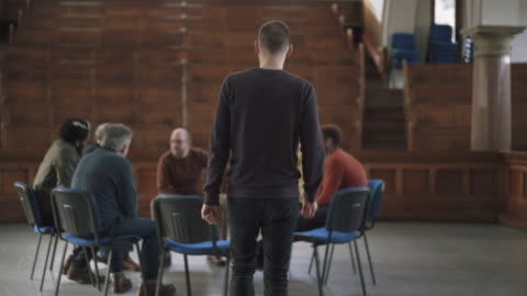 man joining group of men in therapy session - male friendship stock videos & royalty-free footage