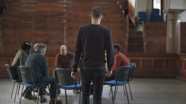 man joining group of men in therapy session - support stock videos & royalty-free footage