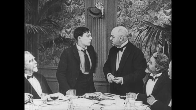 stockvideo's en b-roll-footage met 1921 man (buster keaton) joins a table of scientists at a restaurant and lies in order to get a job - 1921