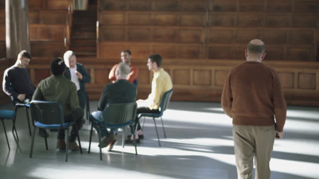 man joins therapy group sat in circle - chair stock videos & royalty-free footage
