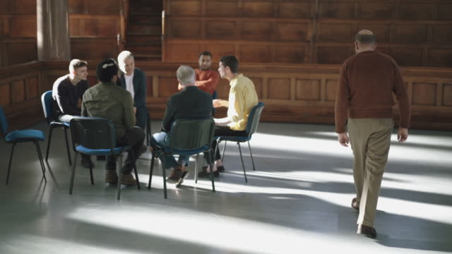 man joins therapy group sat in circle - town hall stock videos & royalty-free footage