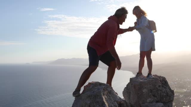 vídeos de stock e filmes b-roll de man joins woman on rock summit, sunrise - calções