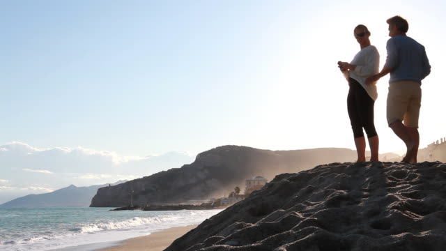 Man joins woman on sand pile, take pictures towards surf
