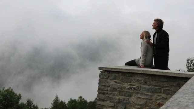 man joins woman on stone wall, watch passing clouds - stone wall stock videos and b-roll footage