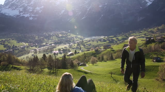 Man joins woman relaxing in grassy mountain meadow, sunrise