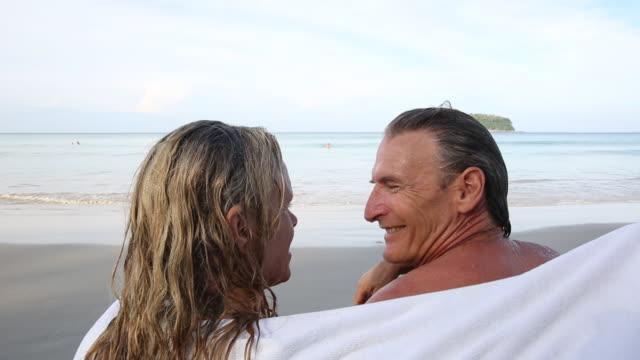 man joins woman under towel near beach edge - asciugamano video stock e b–roll
