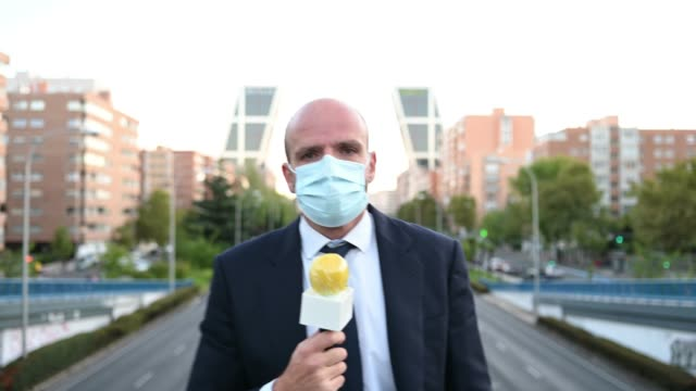 vídeos y material grabado en eventos de stock de man journalist wearing mask with microphone on street in city - journalist