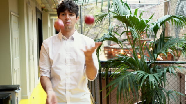 man juggling apples in office - jonglieren stock-videos und b-roll-filmmaterial