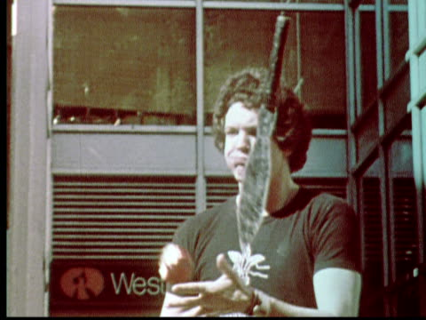 1976 MS ZI CU Man (Penn Jillette of Penn and Teller fame) juggling knives and biting apple / Philadelphia, Pennsylvania, USA