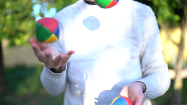 man juggling with colored balls in garden slowmotion - jonglieren stock-videos und b-roll-filmmaterial