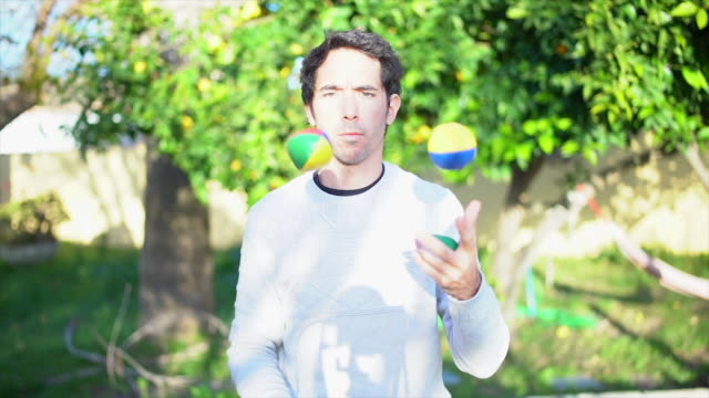 Man juggling with colored balls in garden slowmotion