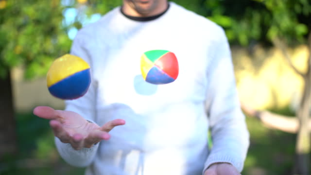 vídeos y material grabado en eventos de stock de man juggling with colored balls in garden - malabarismo