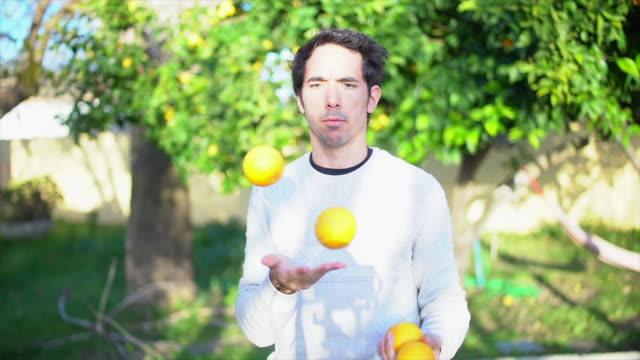 Man juggling with lemmons in garden slowmotion