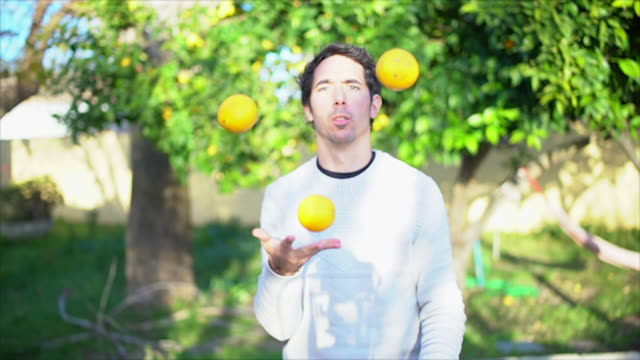 man juggling with lemons in garden slowmotion - jonglieren stock-videos und b-roll-filmmaterial