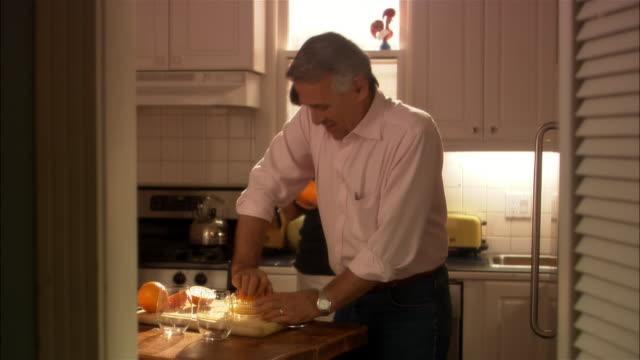 vídeos y material grabado en eventos de stock de man juicing oranges in kitchen while woman talks on mobile phone - t mobile