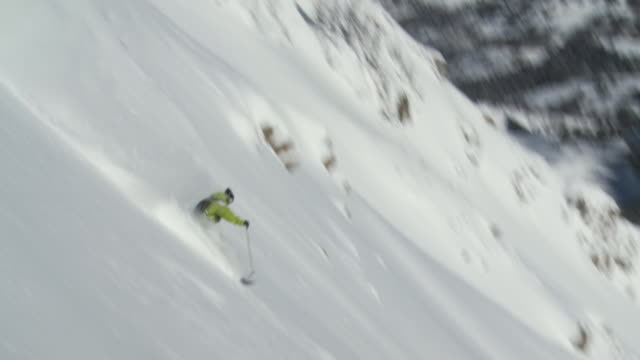 ws ts man jumping and airs off cliff in middle before skiing out bottom / alta, snowbird, utah, usa - ユタ州 アルタ点の映像素材/bロール
