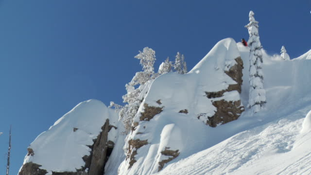 ws zi slo mo man jumping big rock and skiing down in powder snow / alta, snowbird, utah, usa - ユタ州 アルタ点の映像素材/bロール