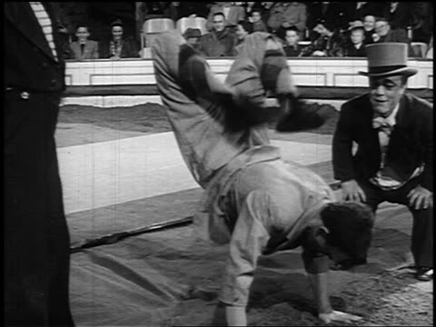 b/w 1955 man jumping + doing handstands as two clowns watch in circus - circus stock videos and b-roll footage