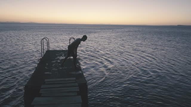 man jumping from a pier at dusk - pantaloncino da bagno video stock e b–roll
