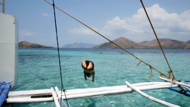 mann springt von einem segelboot in el nido strände - sprung wassersport stock-videos und b-roll-filmmaterial