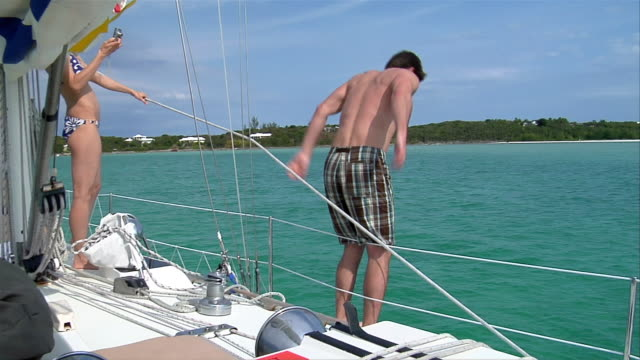 MS, Man jumping from boat into water, rear view, Harbour Island, Bahamas