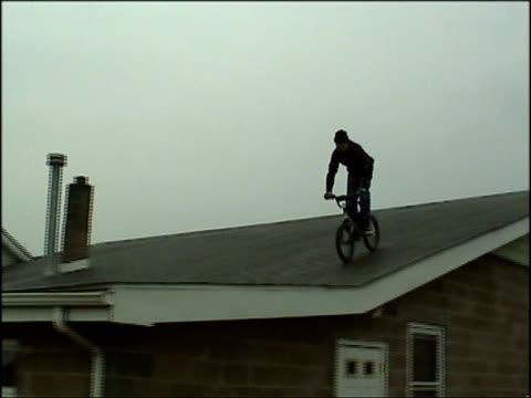 ms, la, pan,  man jumping from building's roof on box bike then  crashing, usa - fallimento video stock e b–roll