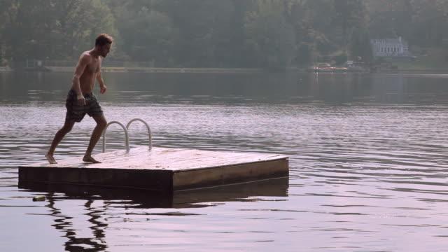 vídeos y material grabado en eventos de stock de man jumping from dock into lake - sólo hombres jóvenes