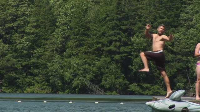 WS SLO MO Man jumping into Alice lake, woman standing on jetty / Squamish, British Columbia, Canada