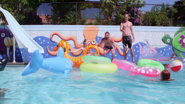 ms slo mo man jumping into inflatable inner tubes in outdoor swimming pool during party with friends on summer afternoon - inner tube stock videos and b-roll footage