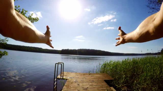 ウェアラブルカメラで湖に飛び込む男.pov。夏のアクティビティ - 溜水点の映像素材/bロール