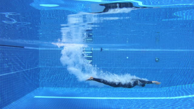 a man jumping into pool. - diving into water stock videos & royalty-free footage