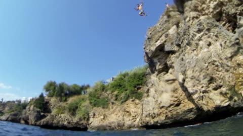 stockvideo's en b-roll-footage met hd: man springen in zee slow motion - klif