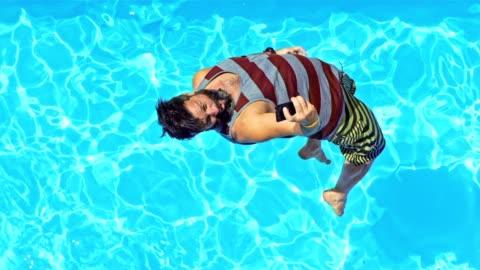 rallent cs uomo saltando in piscina e scattare foto - swimming pool video stock e b–roll