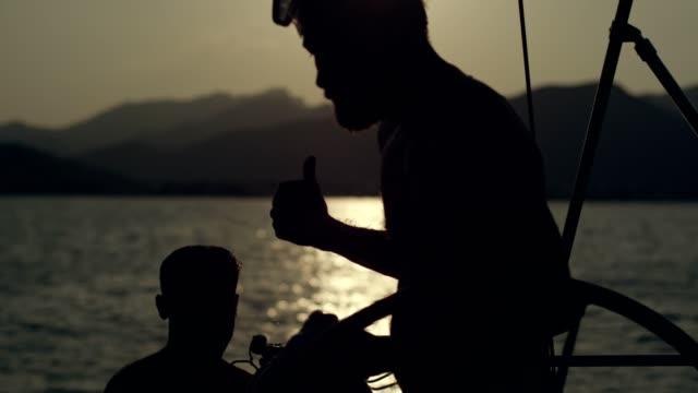 mann von einem segelboot ins meer springen. unter wasser gedreht. - unterwasserkamera stock-videos und b-roll-filmmaterial