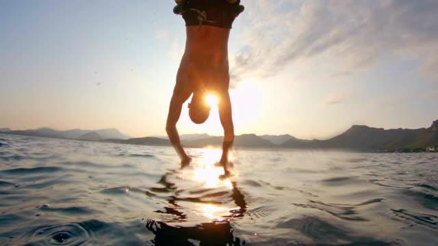 vídeos de stock, filmes e b-roll de homem pulando no mar de um veleiro - debaixo d'água