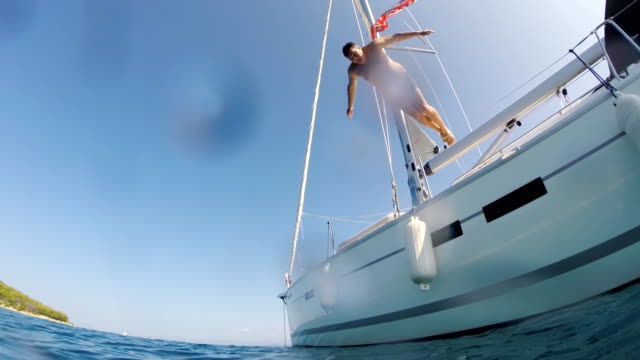 slo mo man jumping into the sea from a sailboat - jumping stock videos & royalty-free footage