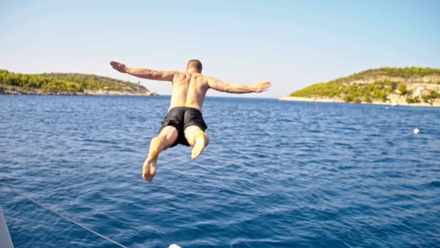 SLO MO Man jumping into the sea from a sailboat