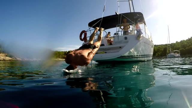 mann springt ins meer von einem segelboot - erfrischung stock-videos und b-roll-filmmaterial