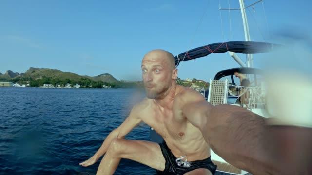 stockvideo's en b-roll-footage met man overboord springen van een zeilboot met draagbare camera - buitenbad