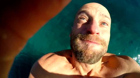 vidéos et rushes de homme se jetant dans la mer tenant gopro - baie eau