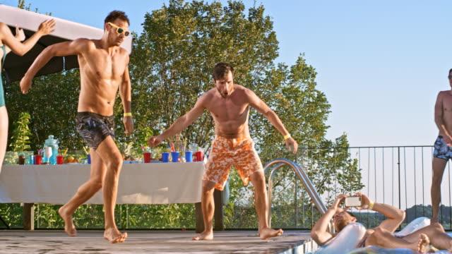 SLO MO DS Man springen in het water op een pool party bij zonsondergang terwijl vrienden zijn juichen voor hem