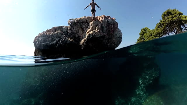 slow motion close up underwater: man jumping into water on head off a high rock in to sea - ledge stock videos & royalty-free footage