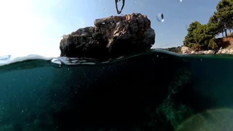 stockvideo's en b-roll-footage met slow motion close-up onderwater: man springen in het water op de kop af een hoge rots in zee - klif