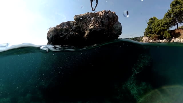 slow motion close up underwater: man jumping into water on head off a high rock in to sea - high up stock videos & royalty-free footage