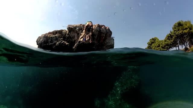 vidéos et rushes de ralenti close up sous l'eau: l'homme sauter dans l'eau sur parer un rocher en mer - rock face