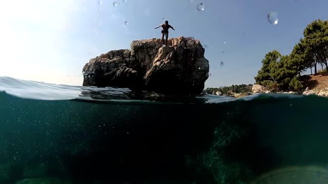 vídeos de stock, filmes e b-roll de câmera lenta, close-up subaquático: homem pulando na água na cabeça de uma rocha alta no mar - falésia